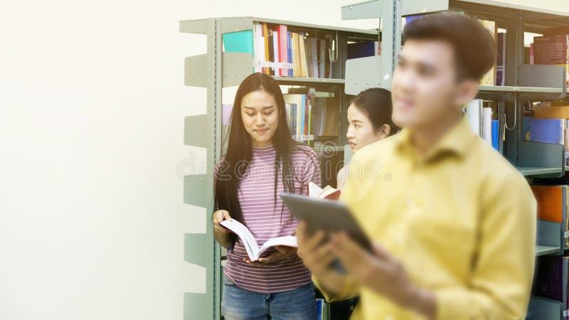 O homem asiático do adolescente lê uma tabuleta com estudantes fala no imagens de stock royalty free