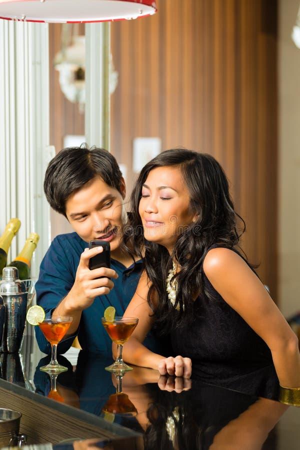 O homem asiático está flertando com a mulher na barra imagens de stock royalty free