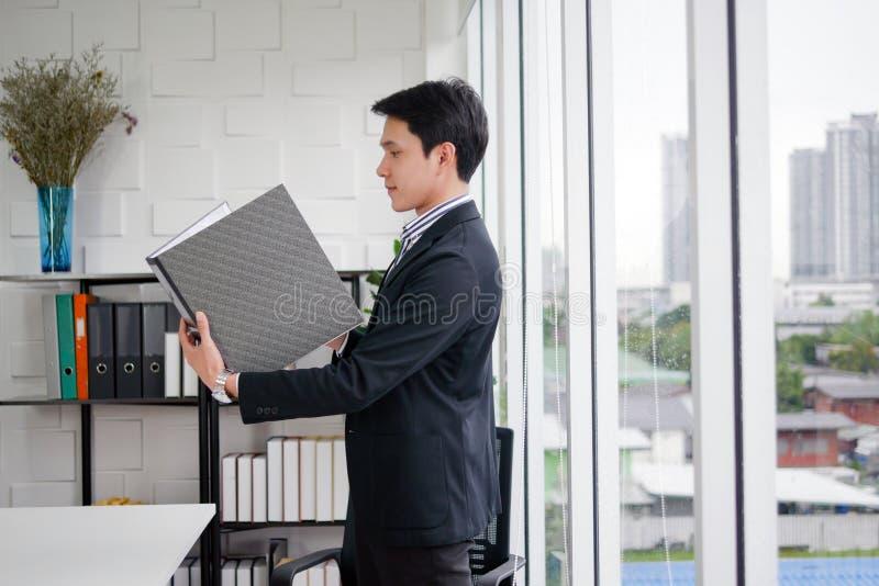 O homem asiático executivo novo é estando e guardando o relatório comercial preto do arquivo na sala moderna do escritório fotos de stock
