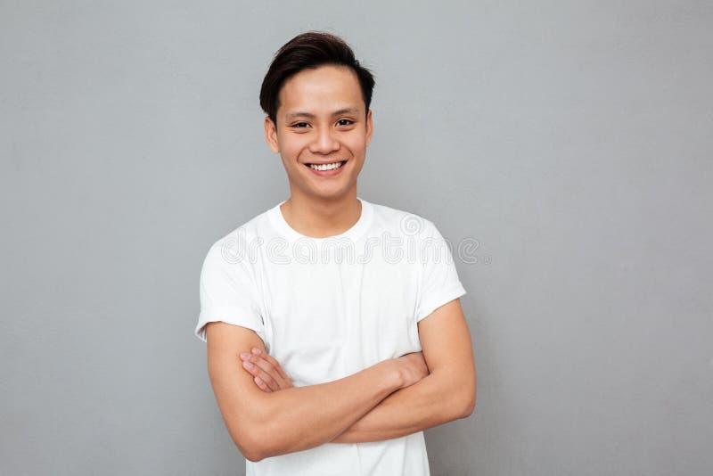 O homem asiático feliz que está com braços cruzou-se sobre a parede cinzenta fotos de stock royalty free