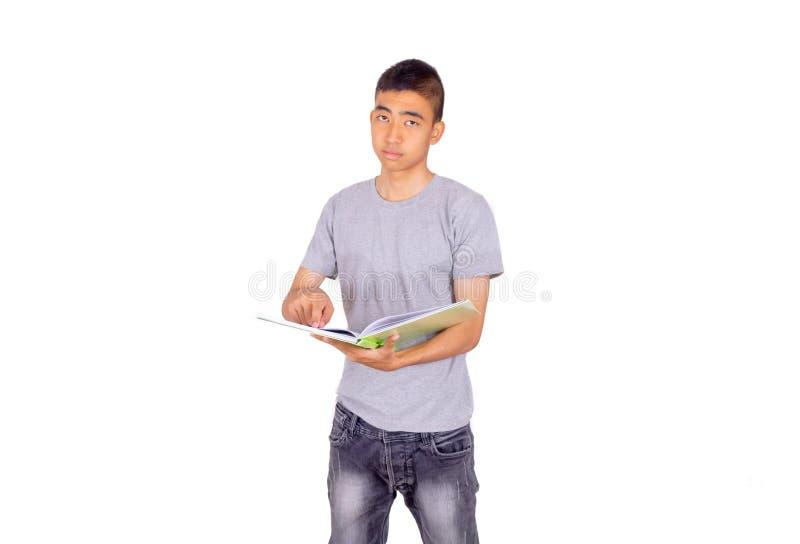 O homem asiático guarda um livro por seus braços e olha sobre ao livro fotografia de stock royalty free