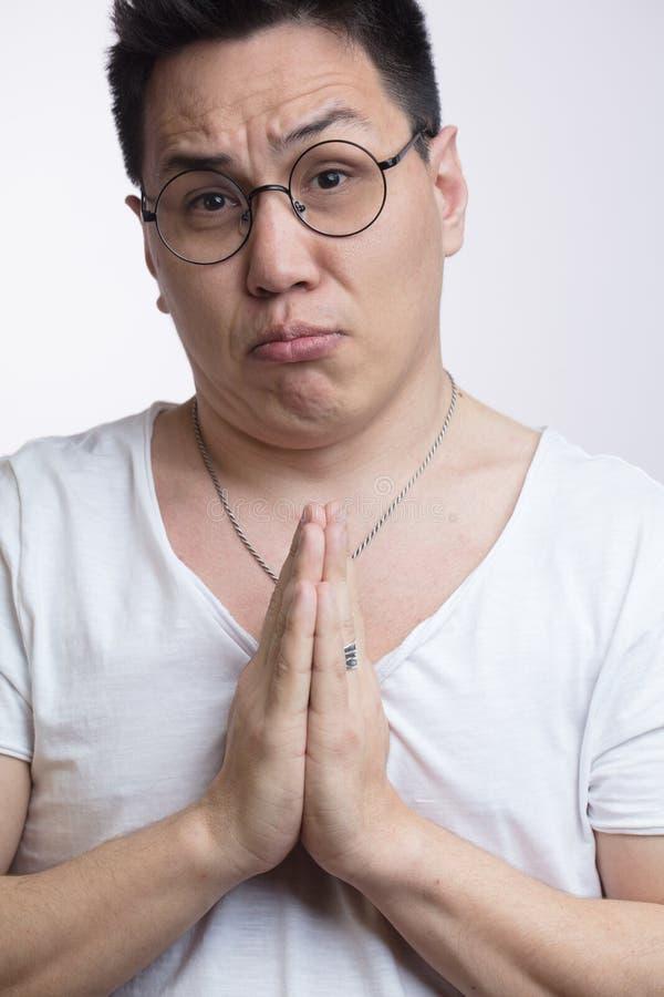 O homem asiático no t-shirt, guardando as mãos reza dentro, implorando pela ajuda ou pedindo a desculpa foto de stock royalty free