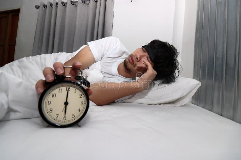 O homem asiático novo com máscara de olho acorda e para o despertador na cama fotografia de stock royalty free