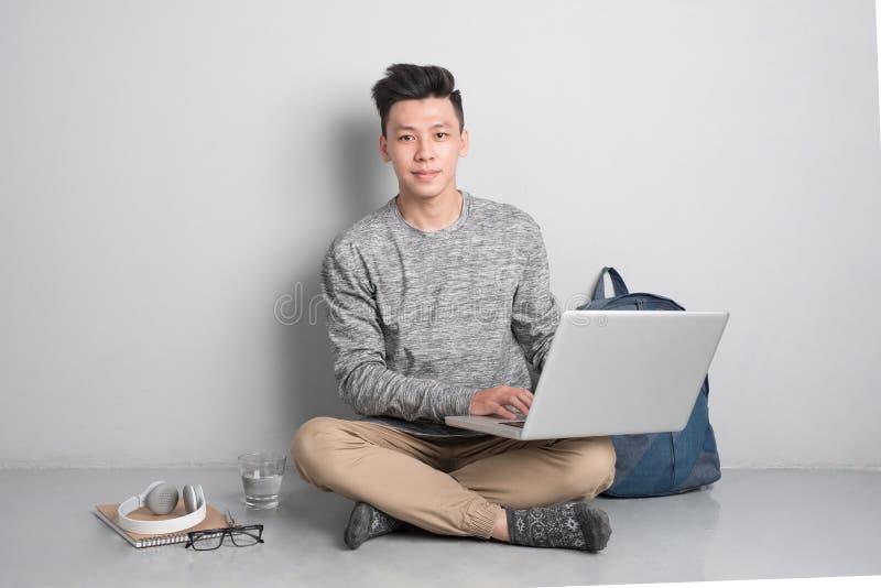 O homem asiático novo na roupa ocasional está usando um portátil, whi de sorriso foto de stock