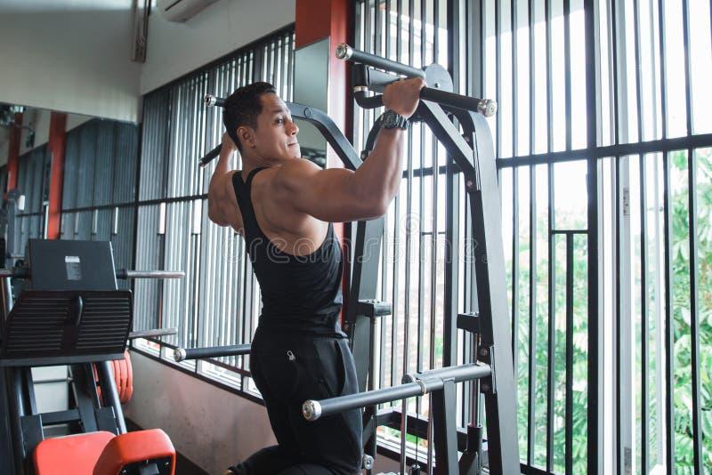 O homem asiático novo que exercita e que faz a tração levanta foto de stock