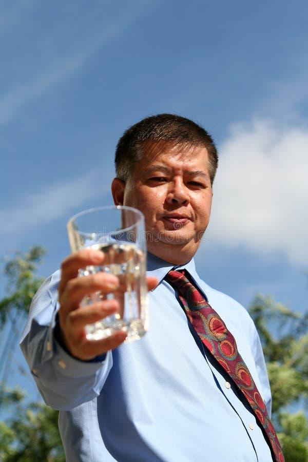 O homem asiático prende um vidro da água sobre o céu azul fotos de stock royalty free