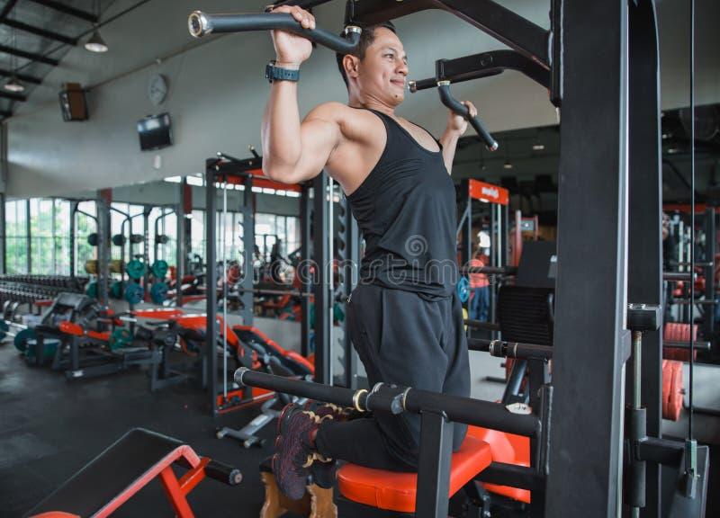 O homem asiático que exercita e que faz a tração levanta foto de stock