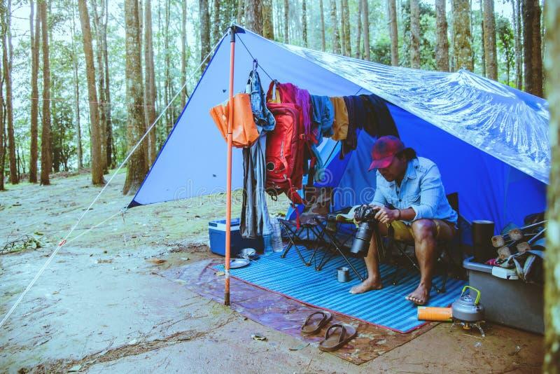 O homem asi?tico relaxa a natureza do curso no feriado Tome um estudo de natureza da imagem na selva que acampa na montanha esta? foto de stock