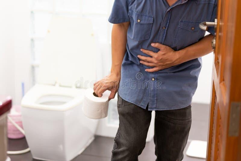 O homem asiático sofre do rolo do tecido da terra arrendada da diarreia ou o papel higiênico perto de uma bacia de toalete, homem foto de stock