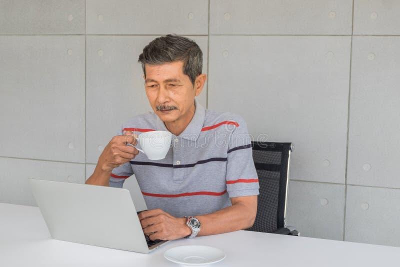O homem asiático superior tem um bigode branco Mão que guarda uma caneca de café, olhar no laptop foto de stock
