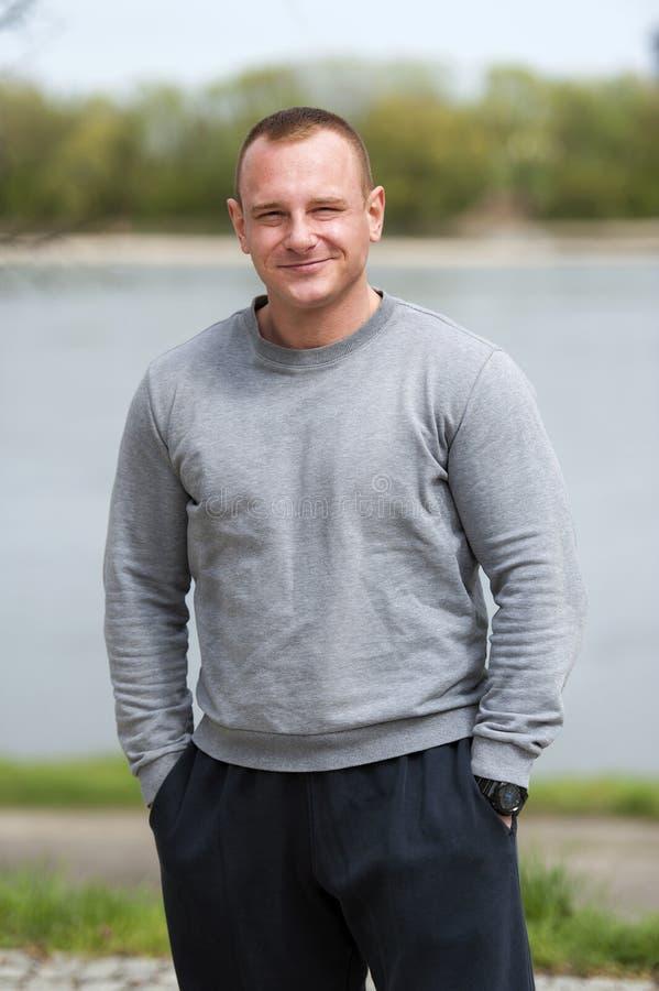 O homem ativo com corpo atlético, exercita exterior no parque Olhar apto fotos de stock royalty free