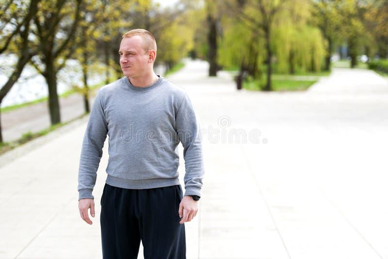O homem ativo com corpo atlético, exercita exterior no parque Olhar apto foto de stock