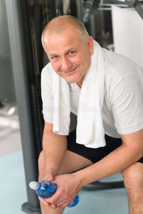 O homem ativo relaxa o assento pela máquina da aptidão imagens de stock royalty free