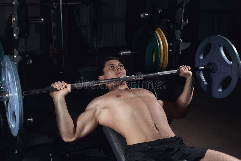 O homem atlético brutal que bombeia acima muscles na imprensa de banco fotos de stock royalty free