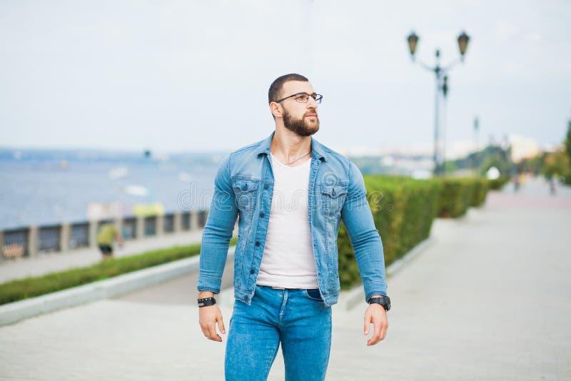 O homem atlético considerável do ajuste nas calças de brim veste o modelo da aptidão fora imagem de stock