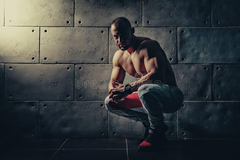 O homem atlético do halterofilista forte que bombeia acima os músculos malha o bodyb fotografia de stock