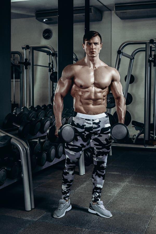 O homem atlético do poder considerável no treinamento da dieta que bombeia acima muscles com peso e barbell Halterofilista forte, fotografia de stock
