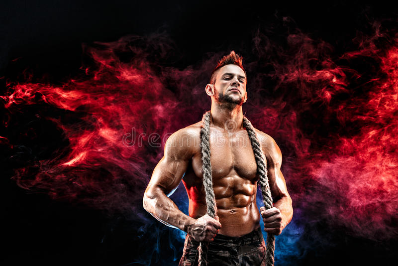 O homem atlético forte com corpo despido em calças militares e a corda no pescoço enegrecem fotografia de stock royalty free
