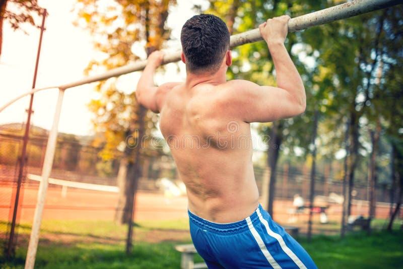 O homem atlético muscular que dá certo no parque, treinamento e fazendo a tração levanta efeito duplo da cor do vintage na foto imagens de stock royalty free