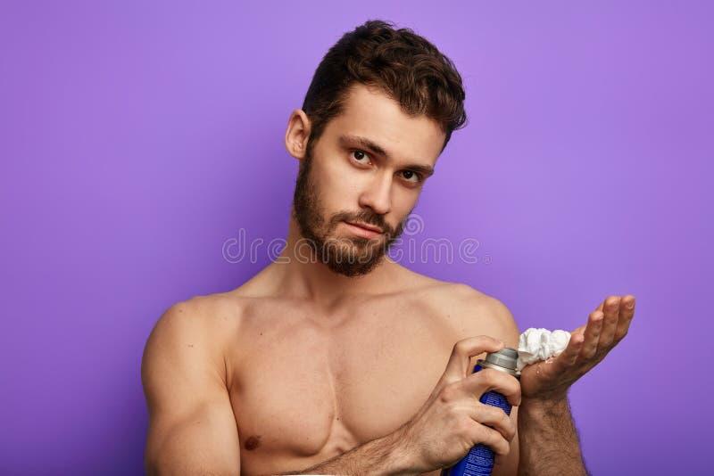 O homem atrativo alegre está aplicando-se barbeando a espuma fotografia de stock royalty free
