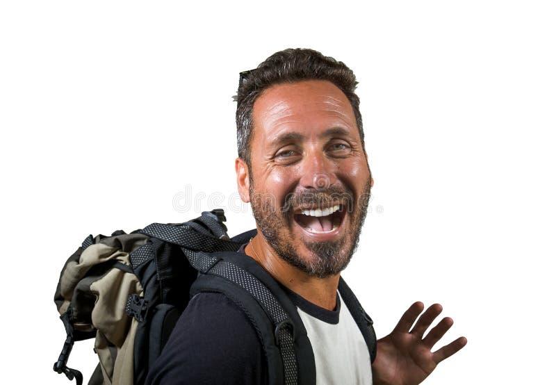 O homem atrativo e feliz novo do mochileiro em sua trouxa 30s ou 40s levando que vai por feriados viaja no turismo e na exploraçã imagem de stock