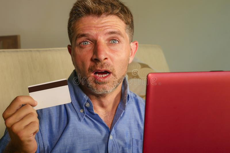O homem atrativo e forçado novo preocupou em casa o sofá do sofá usando o problema do sofrimento do cartão e do laptop de crédito imagens de stock royalty free