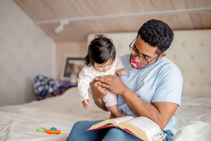 O homem atrativo está guardando um bebê e está lendo um livro imagens de stock