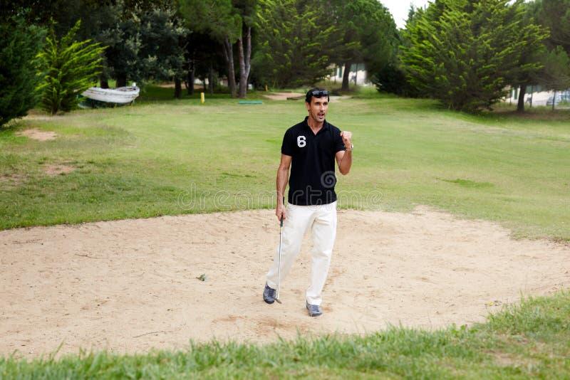 O homem atrativo exulta da vitória em competições do golfe fotografia de stock