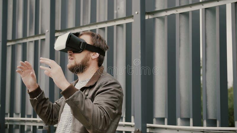 O homem atrativo farpado usa vidros da realidade virtual no espaço urbano 4K fotografia de stock royalty free