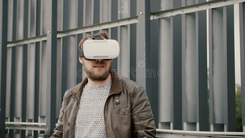 O homem atrativo farpado usa vidros da realidade virtual no espaço urbano 4K fotos de stock