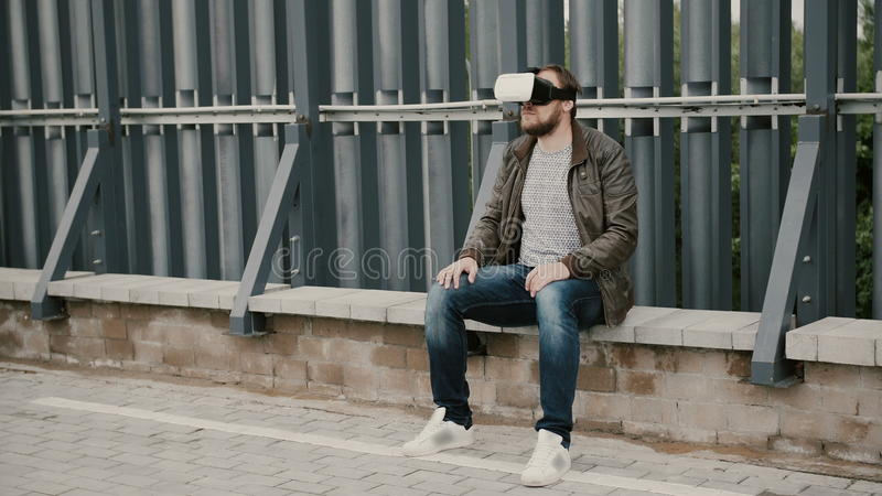 O homem atrativo farpado usa vidros da realidade virtual no telhado, decola seus vidros e caminhadas afastado 4K fotografia de stock