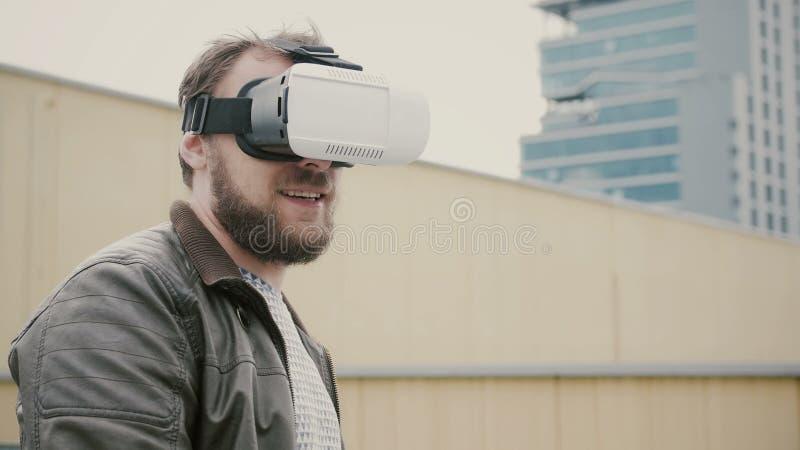 O homem atrativo farpado usa vidros da realidade virtual no telhado 4K imagem de stock