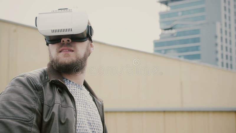 O homem atrativo farpado usa vidros da realidade virtual no telhado 4K fotografia de stock royalty free