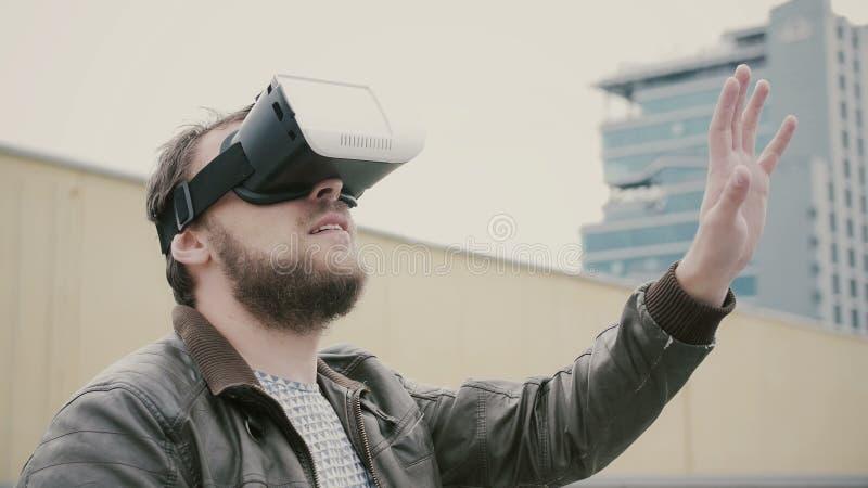O homem atrativo farpado usa vidros da realidade virtual no telhado 4K imagens de stock
