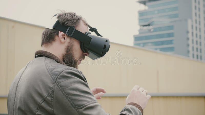 O homem atrativo farpado usa vidros da realidade virtual no telhado 4K fotos de stock