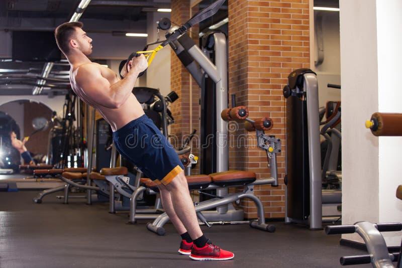 O homem atrativo faz Crossfit para empurrar levanta com as correias da aptidão de Trx no estúdio do ` s do Gym fotografia de stock royalty free