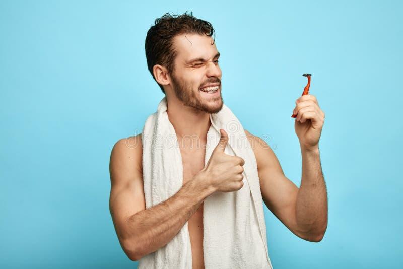 O homem atrativo feliz é satisfeito com uma lâmina nova foto de stock
