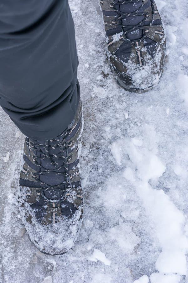 O homem atravessa a neve com as botas mornas do inverno foto de stock royalty free