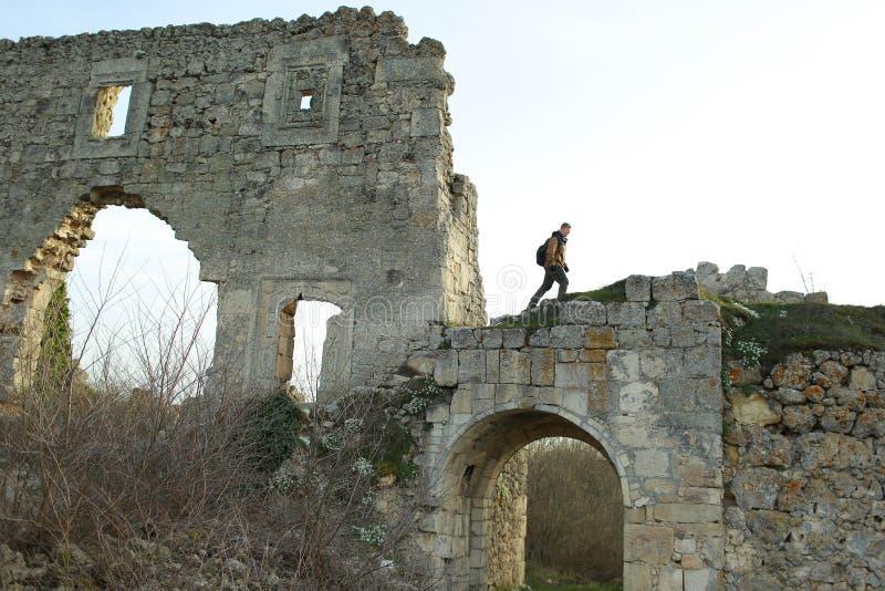O homem aumenta às ruínas de uma fortaleza na cidade da caverna da Mangup-couve fotos de stock royalty free
