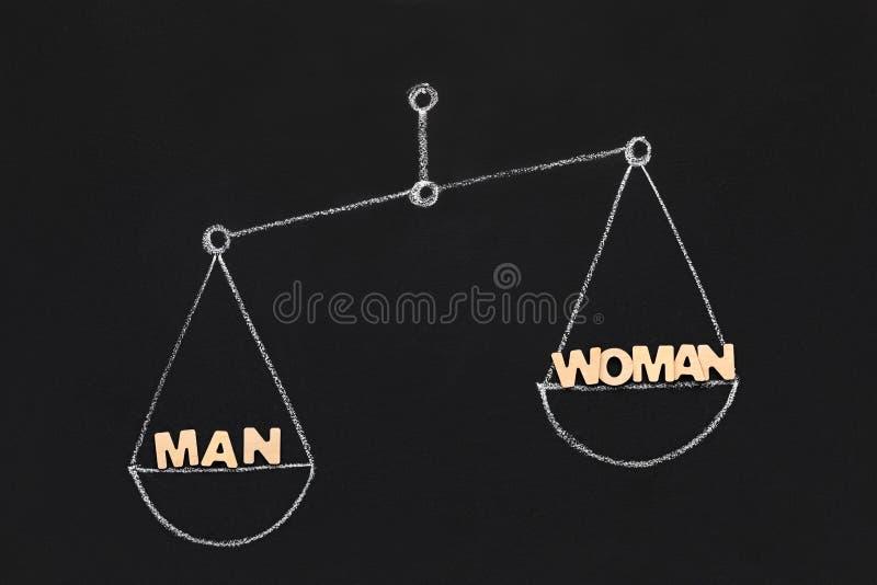 O homem aumenta a mulher em escalas tiradas, quadro-negro foto de stock royalty free