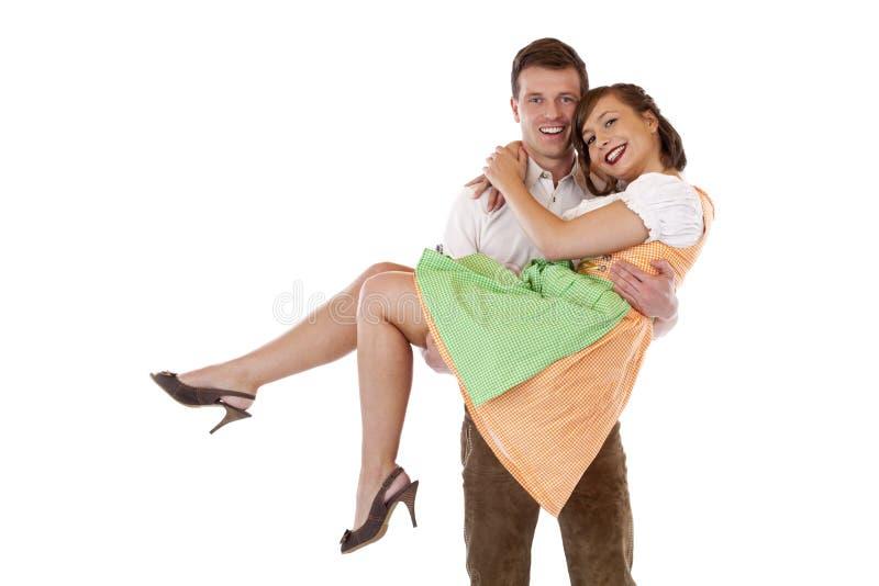 O homem bávaro feliz carreg a mulher com dirndl fotos de stock royalty free