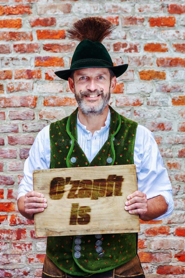 O homem bávaro que guarda um sinal com palavras alemãs para a cerveja é Flowin imagens de stock