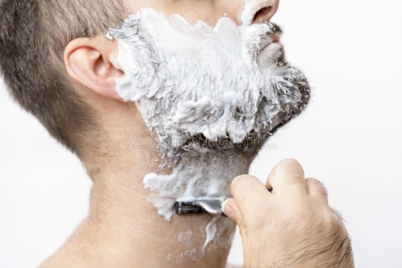 O homem barbeia sua barba com uma l?mina fotografia de stock royalty free
