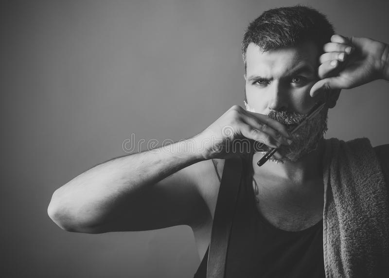 O homem barbeia sua barba Moderno sério no barbeiro, nova tecnologia fotos de stock