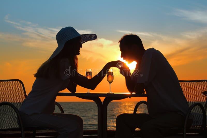 O homem beija a mão à mulher no por do sol fora imagem de stock