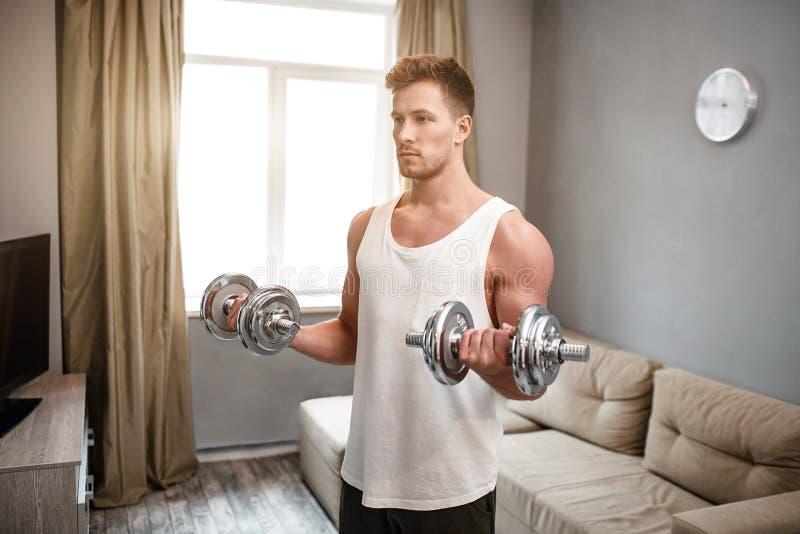 O homem bem-construído novo vai dentro para esportes no apartamento Indivíduo que faz o exercício do peso do bíceps com ambas as  fotografia de stock royalty free