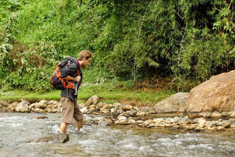 O homem branco novo com trouxa cruza o rio da montanha fotografia de stock royalty free