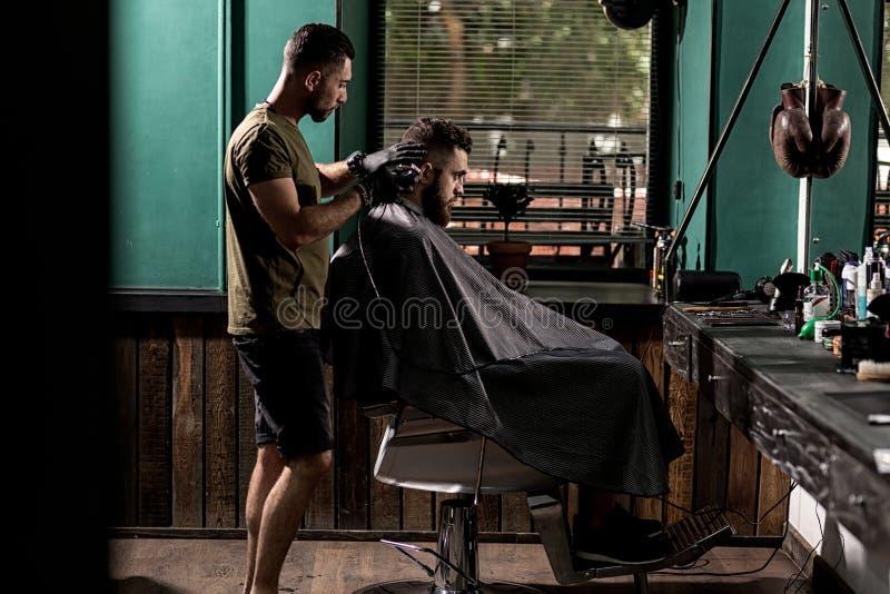 O homem brutal com barba senta-se em um chire em uma barbearia O barbeiro considerável barbeia os cabelos no lado imagens de stock
