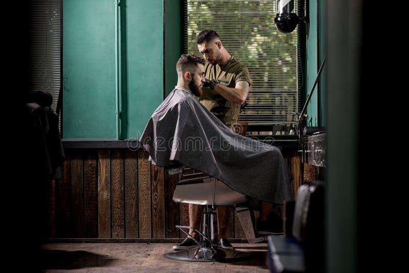 O homem brutal com barba senta-se em um chire em uma barbearia O barbeiro considerável barbeia os cabelos no lado foto de stock