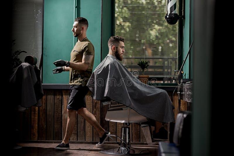 O homem brutal com barba senta-se em um chire em uma barbearia O barbeiro considerável passa ao lado dele fotos de stock royalty free